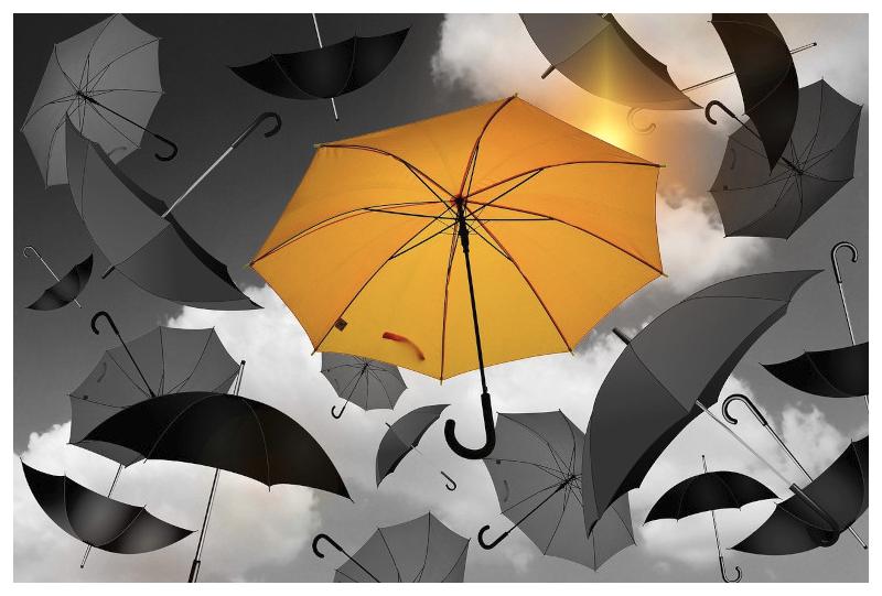 A yellow umbrella among the grey umbrellas